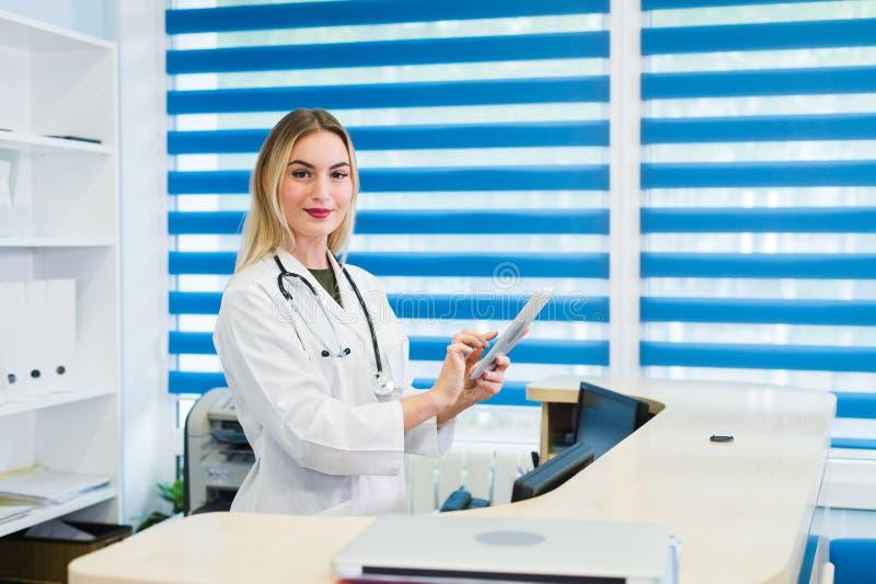 Het glimlachen het vrouwelijke arts schrobt dragen en werkend bij de het ziekenhuisontvangst, schrijft zij een medisch rapport ov royalty-vrije stock fotografie