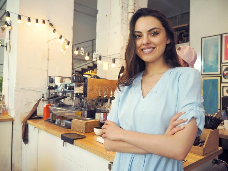 Het glimlachen vrouwelijke barista die espresso voorbereiden bij koffiewinkel stock foto