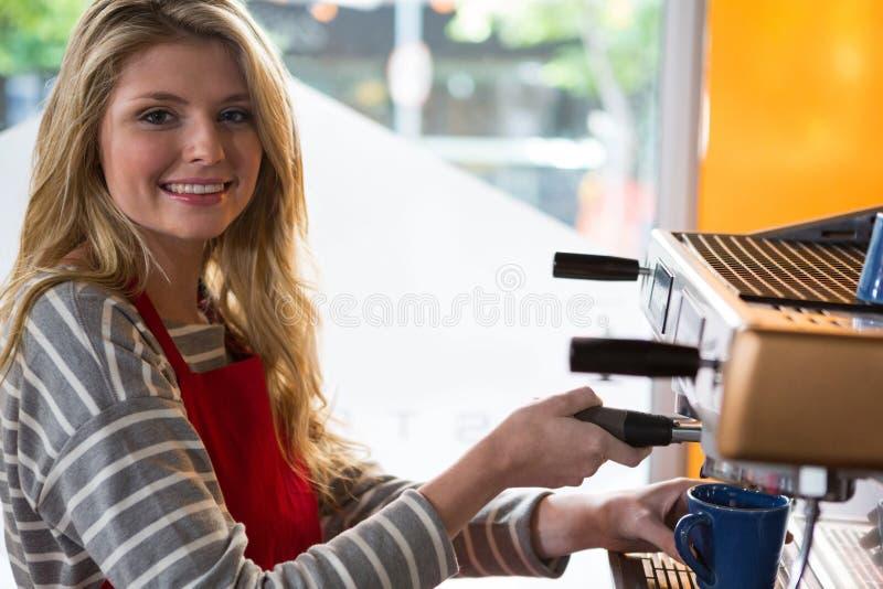 Het glimlachen vrouwelijke barista die koffie met machine voorbereiden stock foto