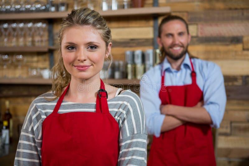 Het glimlachen vrouwelijke barista met mannelijke collega in koffiehuis stock foto's