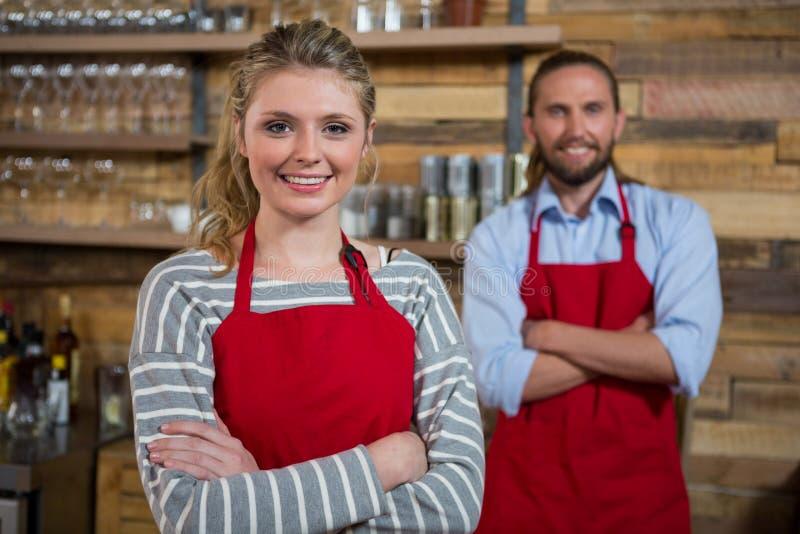 Het glimlachen vrouwelijke barista met mannelijke medewerker in koffiewinkel stock afbeeldingen