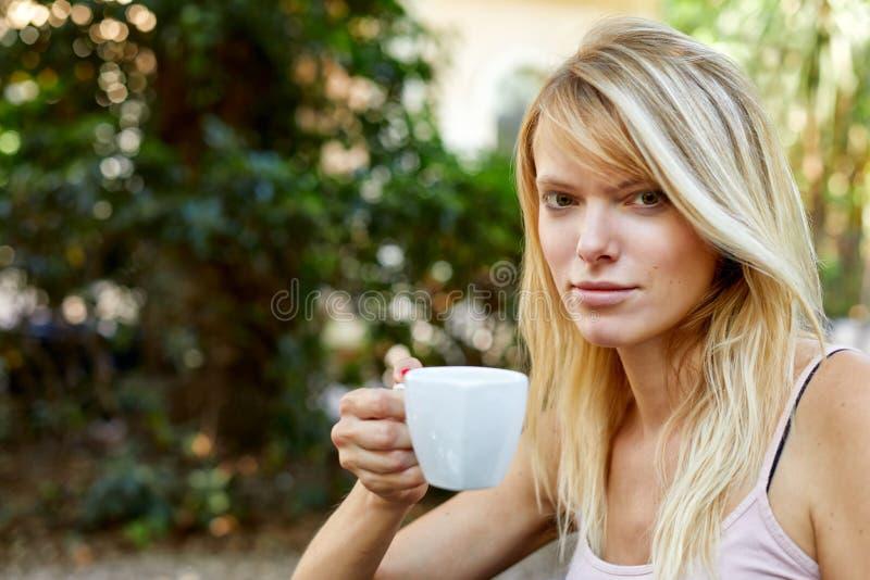 Het glimlachen het vrouwelijke ontspannen met mok in tuin royalty-vrije stock afbeelding