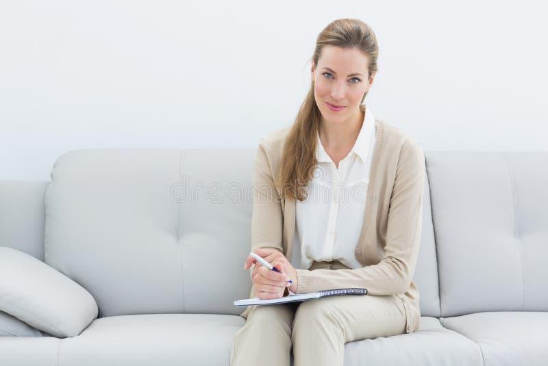 Het glimlachen vrouwelijke psycholoogzitting op bank stock foto