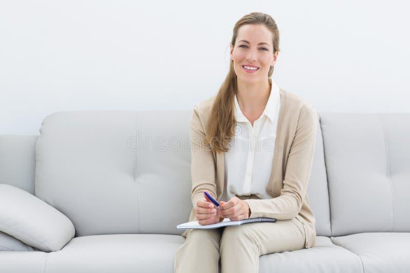 Het glimlachen vrouwelijke psycholoogzitting op bank stock afbeelding