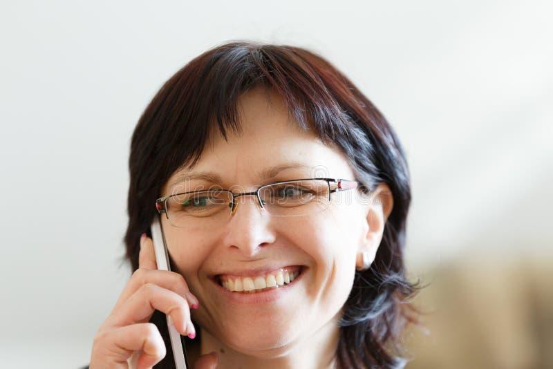Het glimlachen vrouwenvraag op middelbare leeftijd telefonisch stock afbeeldingen