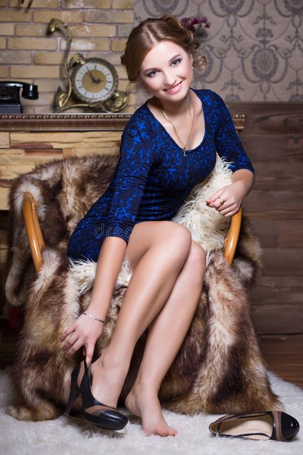 Het glimlachen vrouwenzitting op de stoel stock foto's