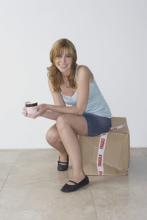 Het glimlachen Vrouwenzitting op Doos met Theekop in Nieuw Huis stock foto's