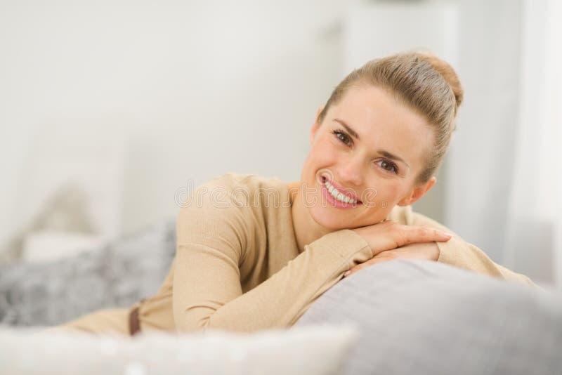 Het glimlachen vrouwenzitting op laag in woonkamer stock foto