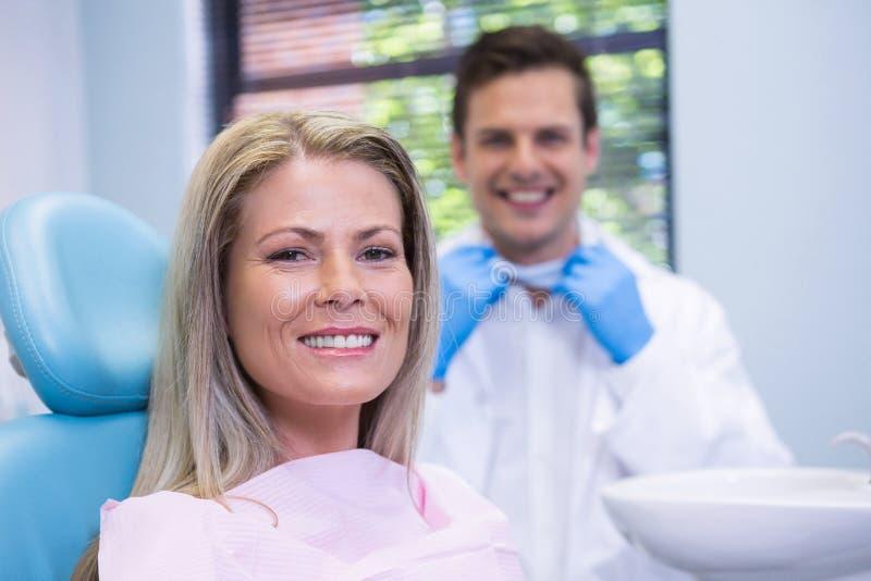 Het glimlachen vrouwenzitting op stoel tegen tandarts bij medische kliniek royalty-vrije stock foto's