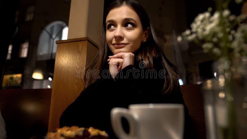 Het glimlachen vrouwenzitting in restaurant en het flirten met bewonderaar, romantische datum royalty-vrije stock fotografie