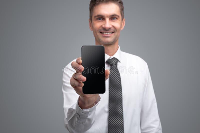 Het glimlachen zakenman het aantonen smartphone stock foto's