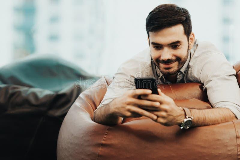 Het glimlachen zakenman het gebruiken en ontspant smartphoneapparaat terwijl thuis het zitten op bank Kerel die van mensen de vro stock fotografie