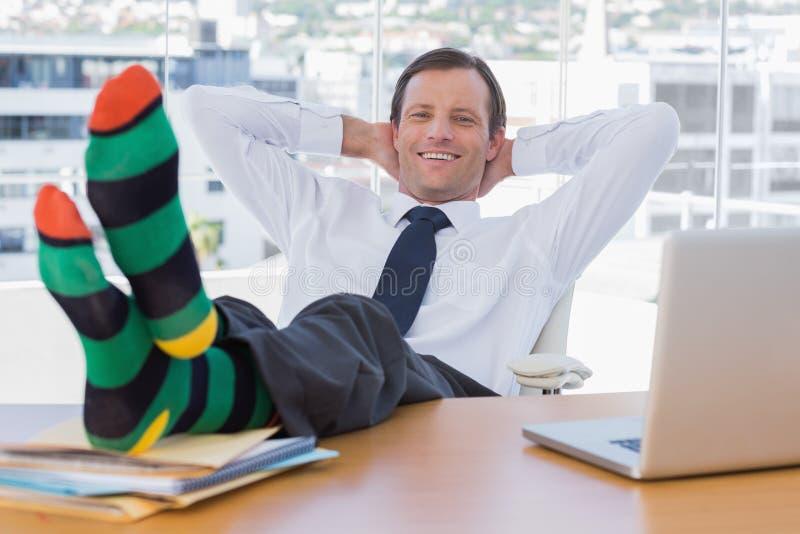 Het glimlachen zakenman het ontspannen met voeten op zijn bureau stock foto's