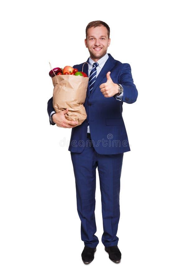 Het glimlachen zakenmanholding het winkelen zakhoogtepunt van groenten op witte achtergrond wordt geïsoleerd die royalty-vrije stock fotografie