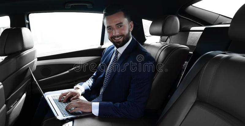 Het glimlachen zakenmanzitting in de achterbank van een prestigieuze auto royalty-vrije stock foto