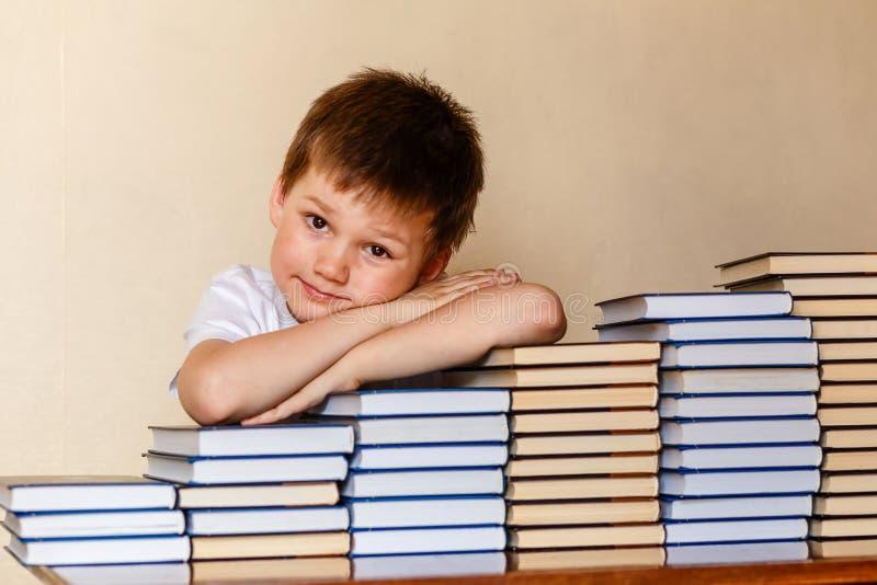 Het glimlachen zes-jaar-oude jongenszitting bij de lijst met zijn handen op boeken royalty-vrije stock afbeeldingen