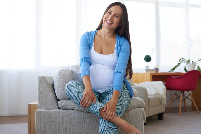 Het glimlachen het zwangere vrouw rusten van bank in woonkamer royalty-vrije stock foto's