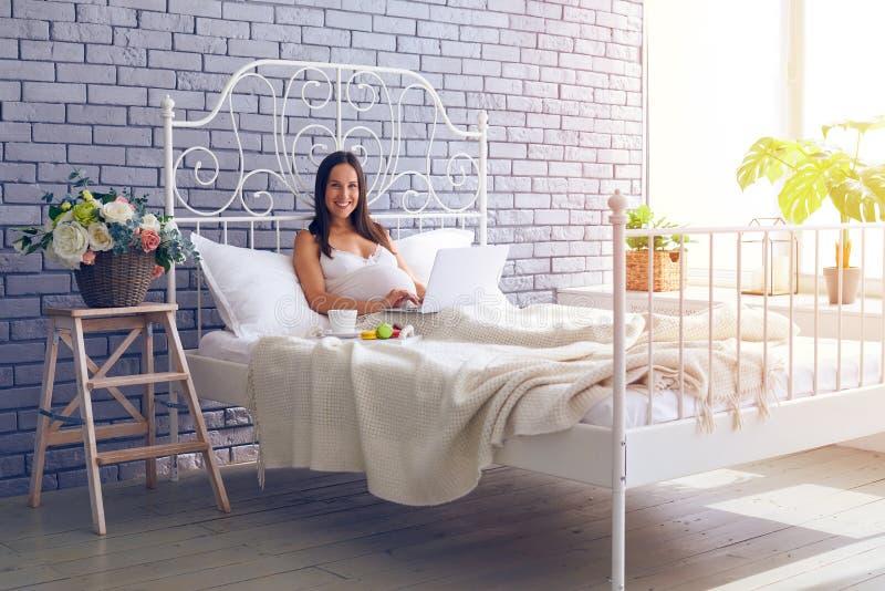 Het glimlachen zwangere vrouwenzitting op bed met laptop, die breakf hebben stock afbeeldingen