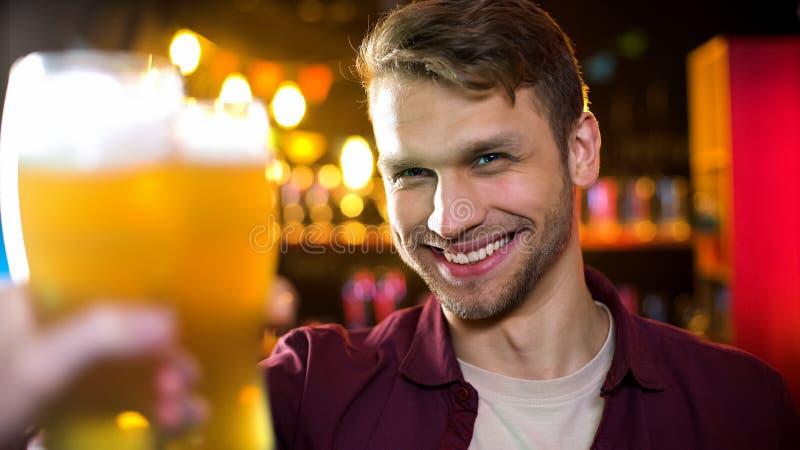 Het glimlachend glazen van het mensen de clinking bier met vriend, resulteert genieten van tijd in bar stock afbeeldingen