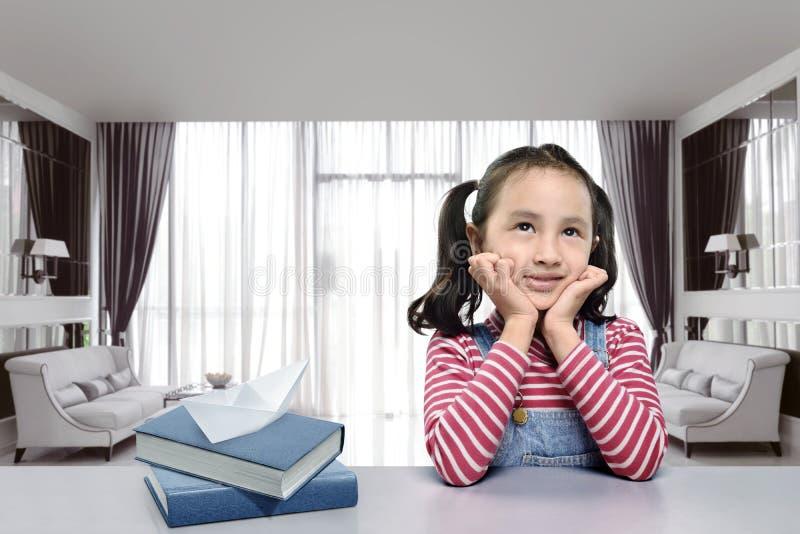 Het glimlachende Aziatische meisje met boek veronderstelt iets royalty-vrije stock afbeelding