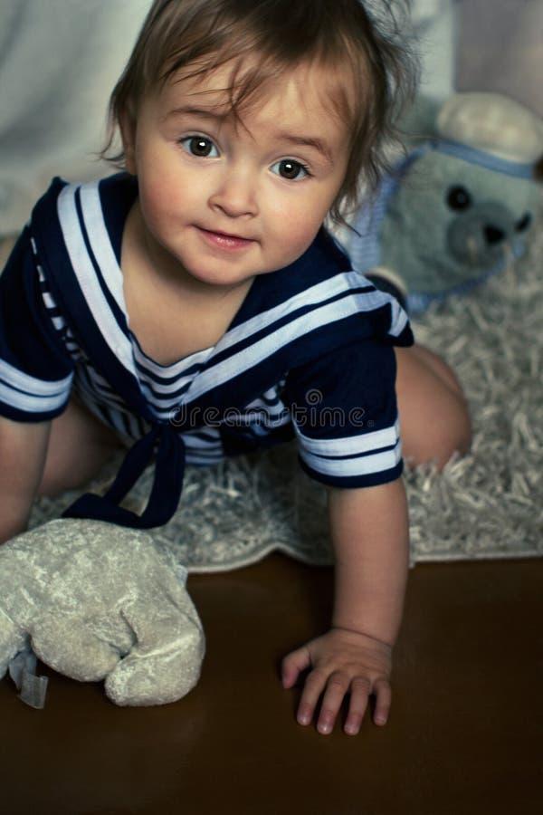 Het glimlachende babymeisje in het zeevaart gestreepte vest zit op carpe stock foto's