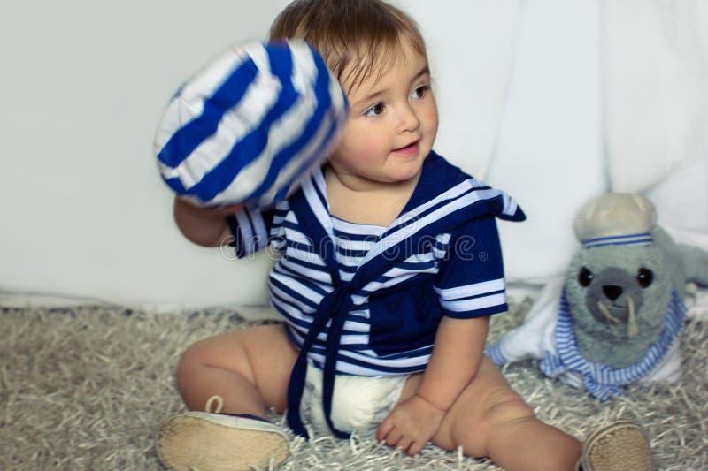 Het glimlachende babymeisje in het zeevaart gestreepte vest zit op carpe royalty-vrije stock foto