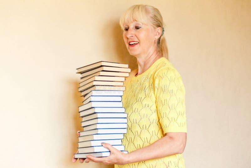 Het glimlachende bejaarde houdt stapel boeken stock afbeeldingen