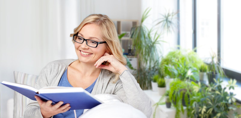 Het glimlachende boek en de zitting van de vrouwenlezing op laag royalty-vrije stock foto