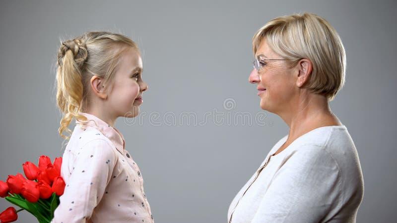 Het glimlachende boeket van meisjes verbergende bloemen, huidig aan geliefde grootmoeder, zorg royalty-vrije stock fotografie