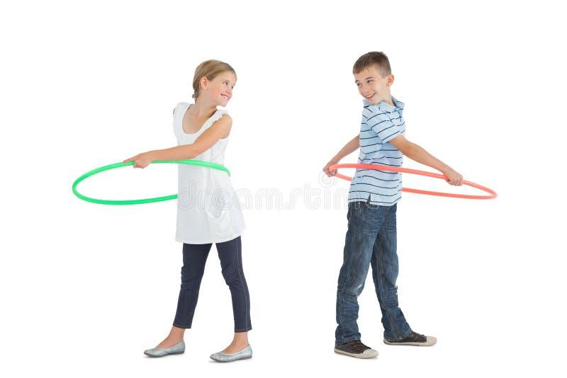 Het glimlachende broer en zuster spelen met hulahoepel royalty-vrije stock fotografie