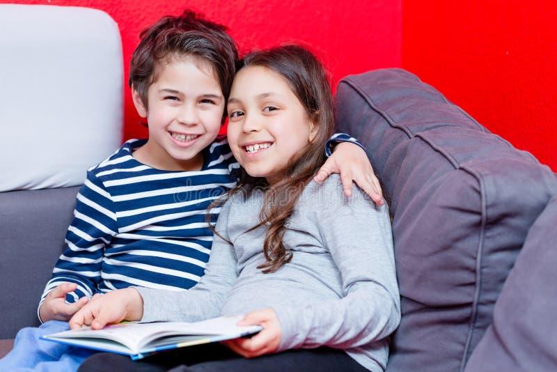 Het glimlachende broer en zusterboek van het holdingsverhaal royalty-vrije stock afbeelding