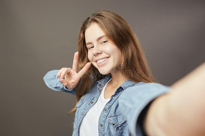 Het glimlachende bruin-haired meisje gekleed in een wit t-shirt en een jeansoverhemd toont v zingt en een selfie op grijs maakt stock afbeelding