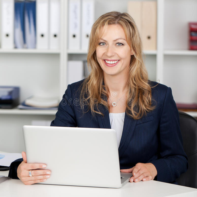 Het glimlachende Bureau van Onderneemsterusing laptop at royalty-vrije stock foto's