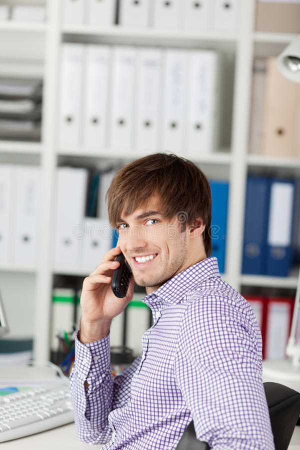 Het glimlachende Bureau van Zakenmanusing phone in royalty-vrije stock afbeeldingen