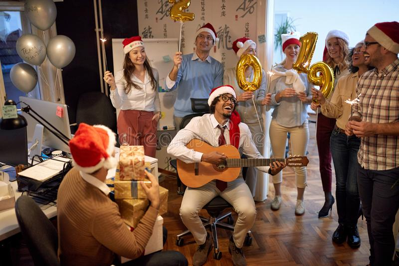Het glimlachende commerciële team heeft pret en het dansen in Kerstmanhoed bij Kerstmispartij stock fotografie