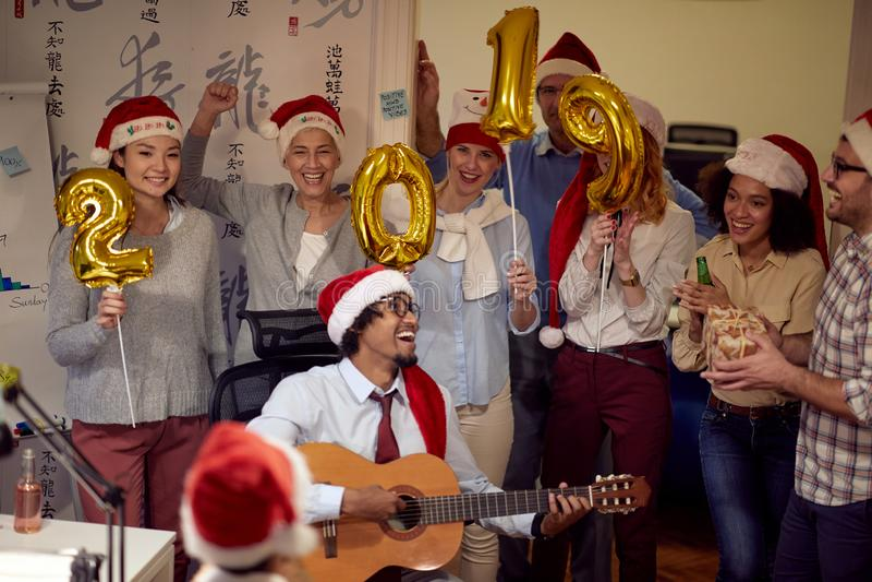 Het glimlachende commerciële team heeft pret en het dansen in Kerstmanhoed bij Kerstmispartij royalty-vrije stock foto