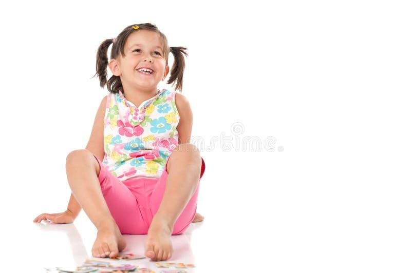 Het glimlachende gelukkige meisje zit royalty-vrije stock afbeelding