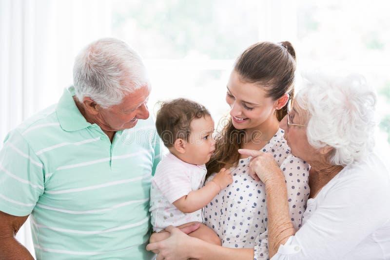 Het glimlachende grootouders en moeder spelen met baby stock afbeelding