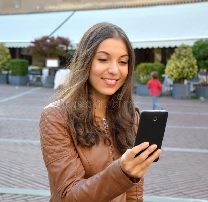 Het glimlachende hipster meisje leest prettig tekstbericht van haar vriend op mobiele telefoon openlucht royalty-vrije stock afbeeldingen