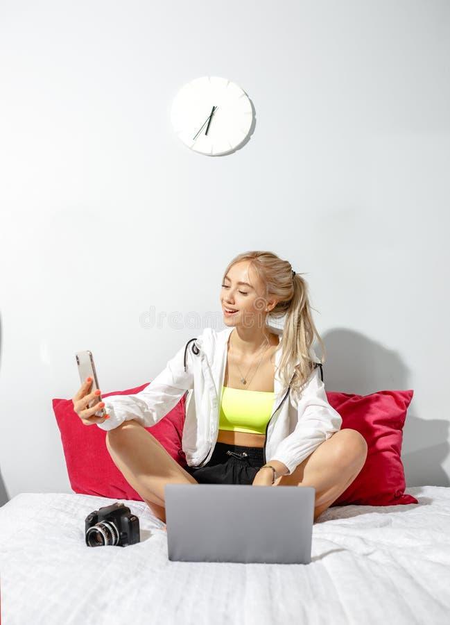 Het glimlachende jonge meisje blogger gekleed in modieuze kleren neemt een selfie op haar smartphone voor haar blogzitting op stock fotografie