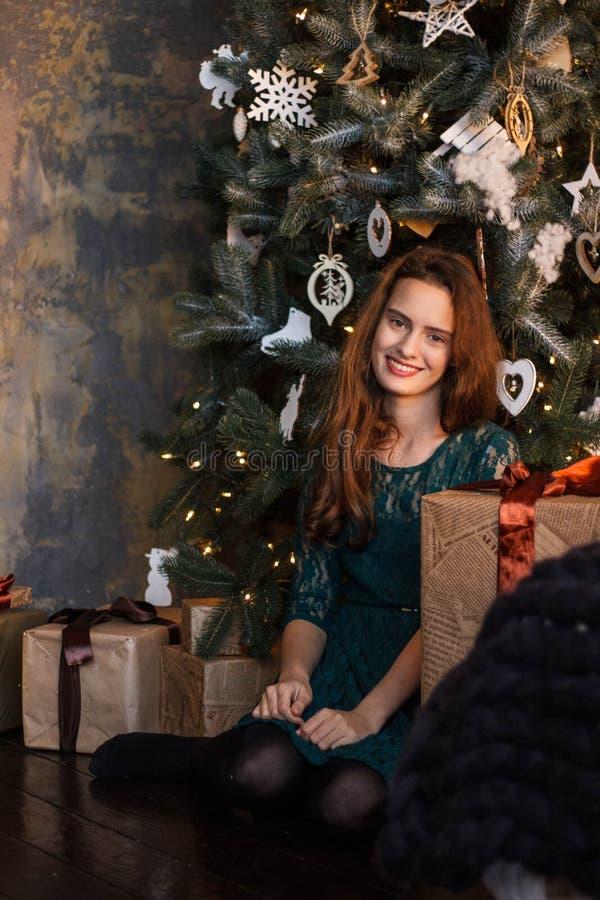 Het glimlachende jonge meisje in groene kleding met stelt voor en giftdozen onder de Kerstboom royalty-vrije stock afbeeldingen