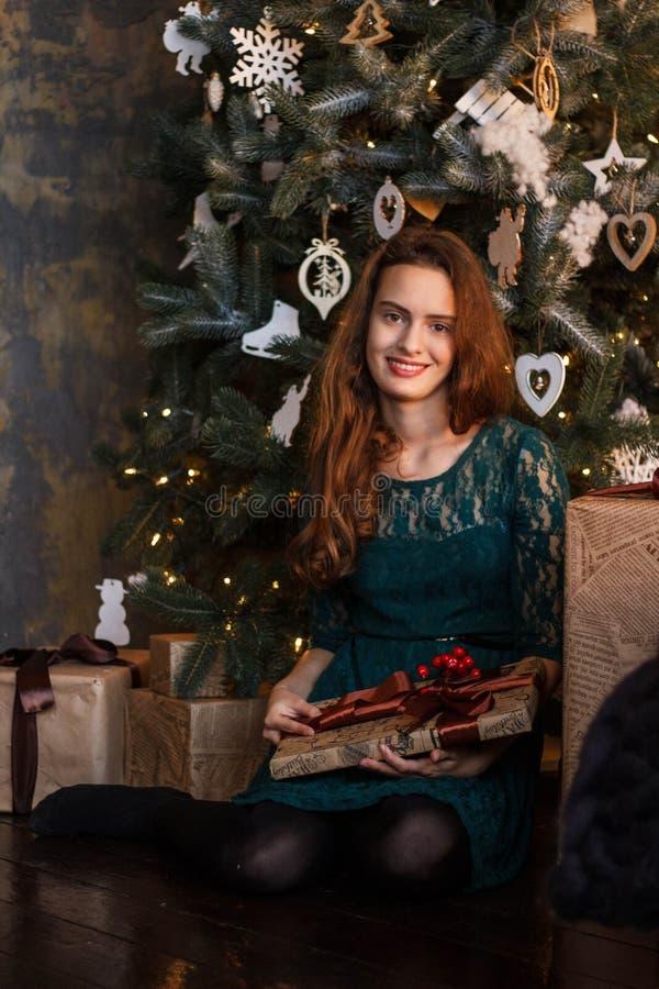 Het glimlachende jonge meisje in groene kleding met stelt voor en giftdozen onder de Kerstboom royalty-vrije stock fotografie
