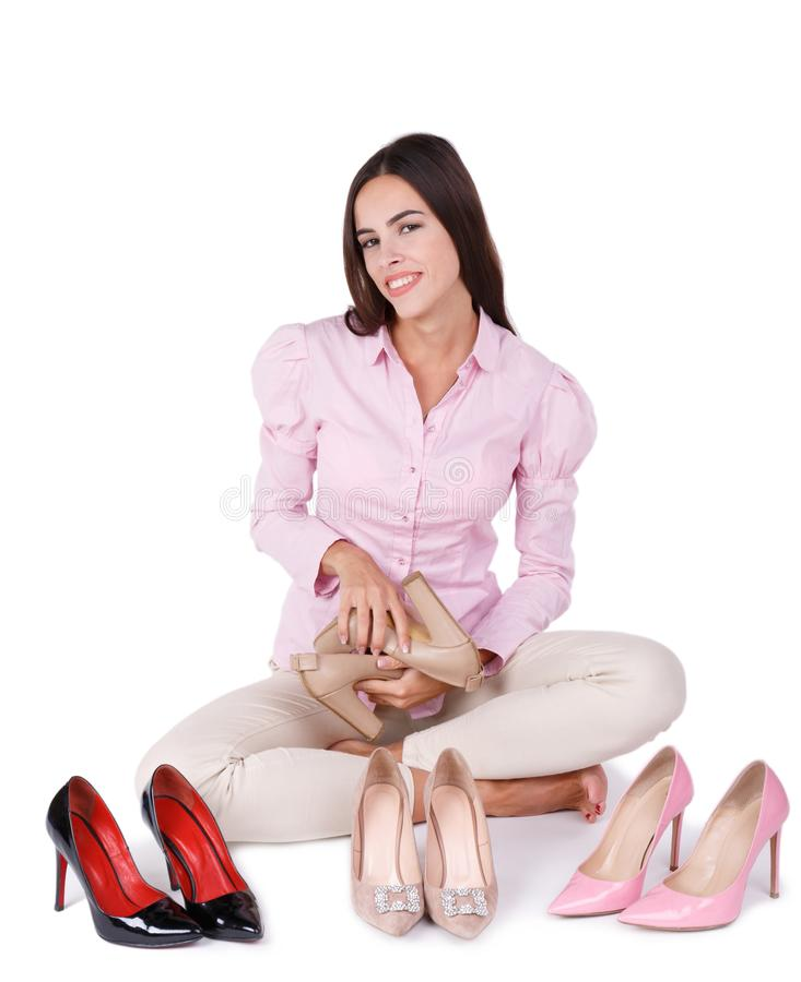 Het glimlachende jonge meisje stelt vier die paren high-heeled schoenen voor op een witte achtergrond worden geïsoleerd royalty-vrije stock foto