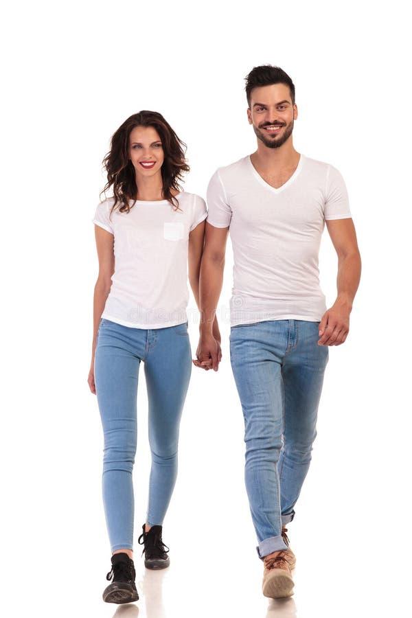 Het glimlachende jonge toevallige paar loopt vooruit stock foto's