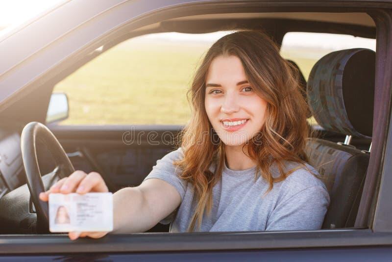Het glimlachende jonge wijfje met prettige verschijning toont trots haar bestuurdersvergunning, zit in nieuwe auto, die jonge one royalty-vrije stock foto's