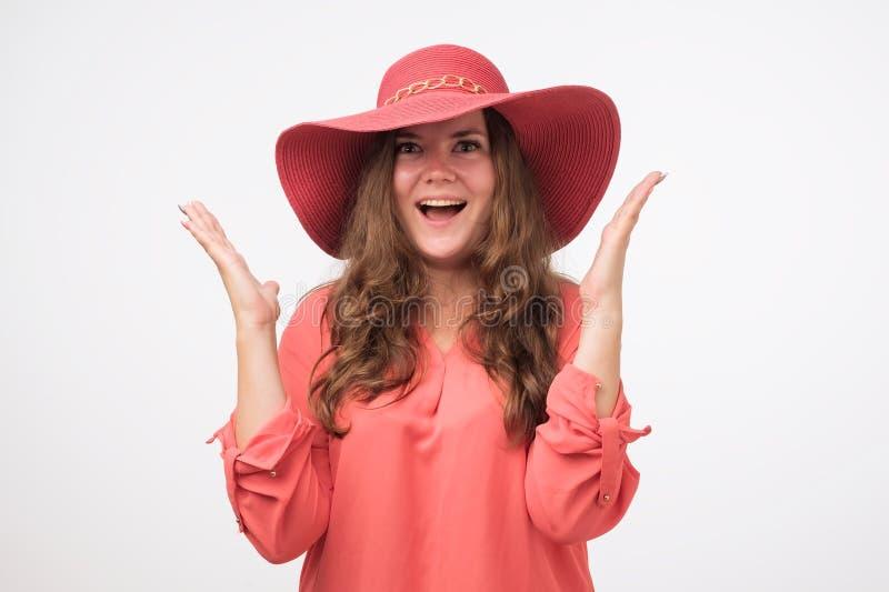 Het glimlachende Kaukasische mollige meisje in een hoed met natuurlijk maakt omhooggaand en rood overhemd bekijkend camera Zij ge stock foto's