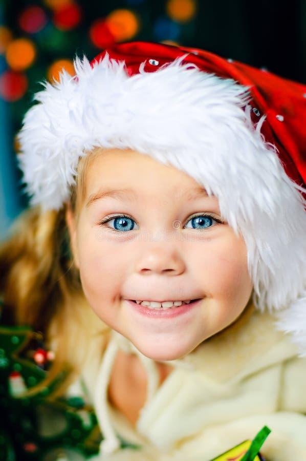 Het glimlachende kind in de hoed van de Kerstman heeft Kerstmis royalty-vrije stock afbeelding