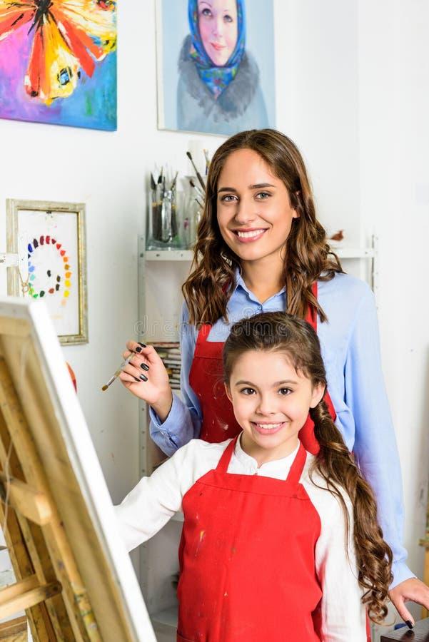 het glimlachende leraar en leerlings schilderen samen in workshop van stock fotografie