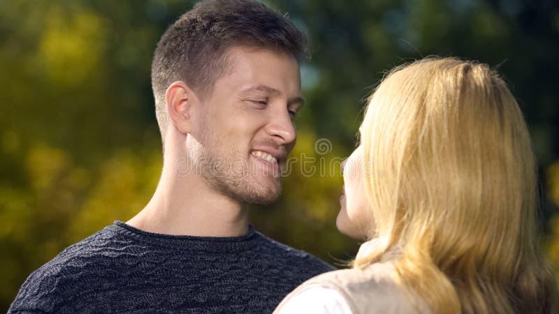 Het glimlachende mannetje die geliefde vrouw, het voelen bekijken houdt van en geluk, samenhorigheid stock afbeeldingen