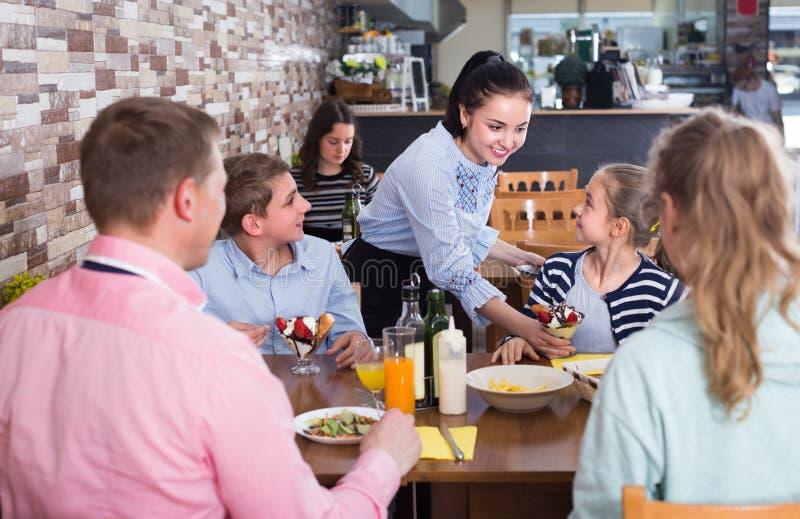 Het glimlachende meisje brengt heerlijk dessert aan jonge bezoekers stock afbeelding